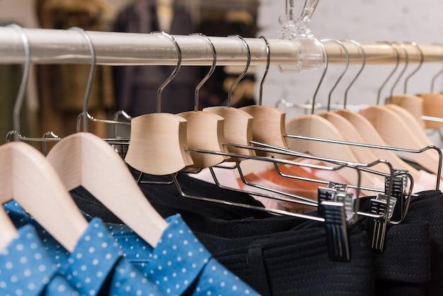 Houten hangers met kleren in boetiekwinkel close-up