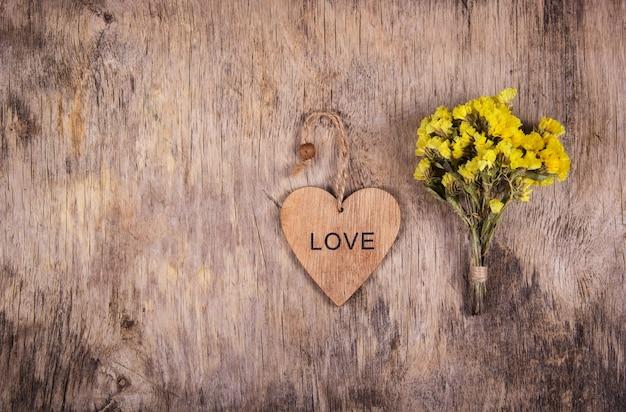 Houten hart en gele bloemen op een oude versleten houten achtergrond