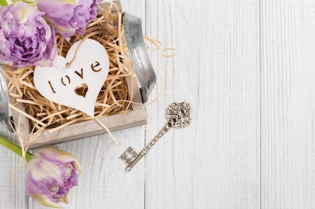 Houten hart in vintage geschenkdoos met sleutel en paarse tulpen
