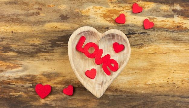 Houten hart met het woord love binnen en kleine rode harten.