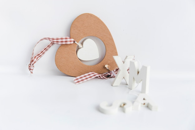 Houten hart vorm ornament met xmas tekst geïsoleerd op witte achtergrond