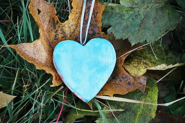 Houten hartdecoratie in de tuin op de achtergrond van de herfstaard