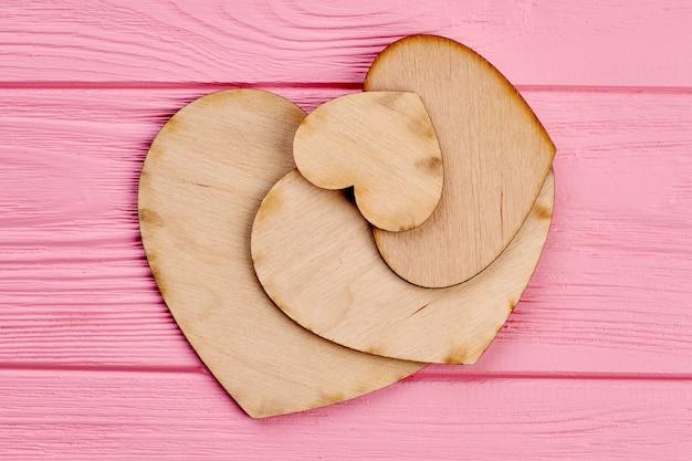 Houten harten op roze houten achtergrond. verschillende maten multiplex harten op kleurrijk gestructureerd hout.