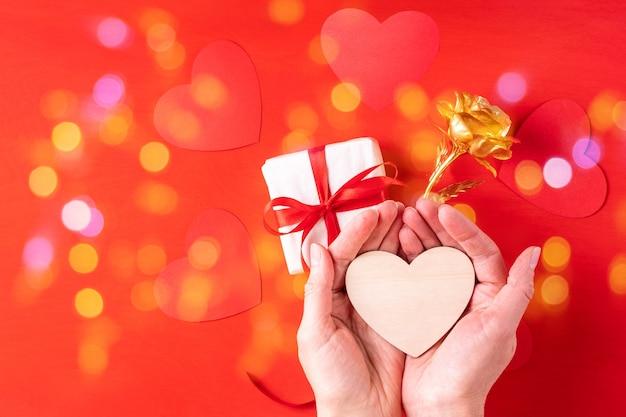 Houten hartvorm in palmen boven een geschenk en een geelgouden roos een symbool van liefde, relaties, familie op een rood oppervlak met bokeh, kopie ruimte. valentijnsdag geschenk