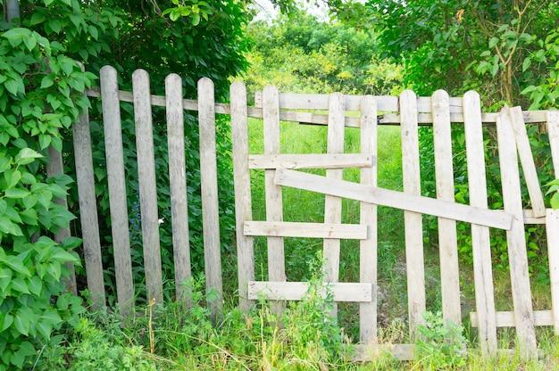 Houten hek in een tuin vol bomen