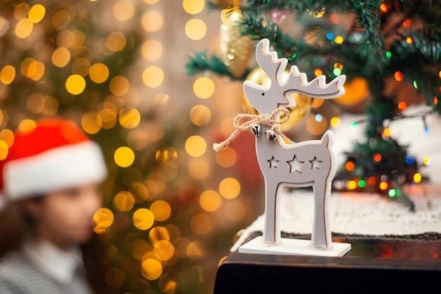 Houten hert als kerstsymbool op de piano, sfeer van de feestdagen. felle lichten, feestelijke decoratie en vrouwelijke pianist op de achtergrond.