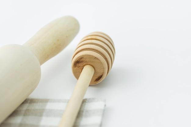 Houten honing dipper deegroller op geruite katoenen keukenhanddoek. bake essentials