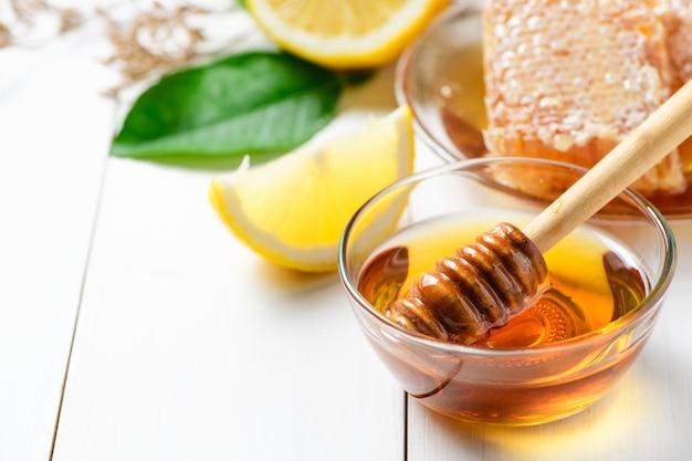 Houten honingsdipper in een kom met honing
