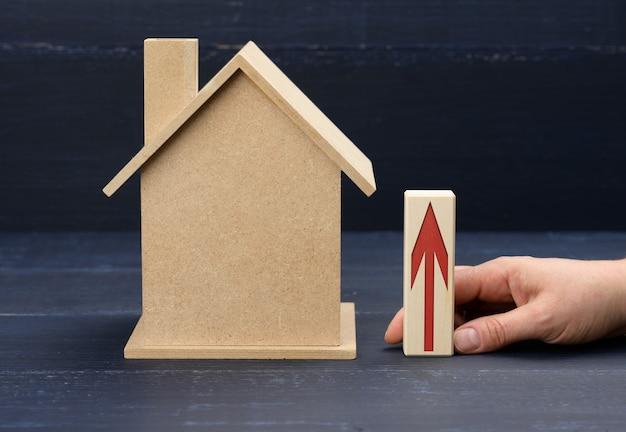 Houten huis en een vrouwelijke hand houdt een balk met een rode pijl vast