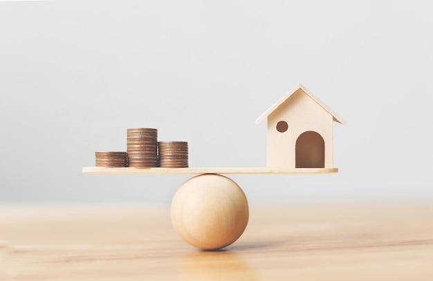 Houten huis en geldmuntstukkenstapel op houten schaal. onroerend goed investeringen en huis hypotheek financiële onroerend goed concept