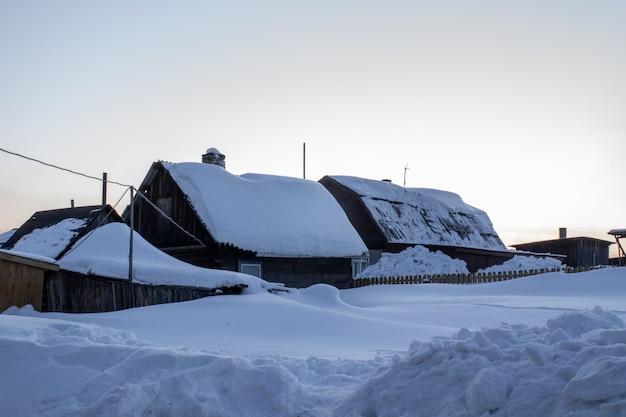 Houten huis in de winter. winterlandschap. winter in siberië.