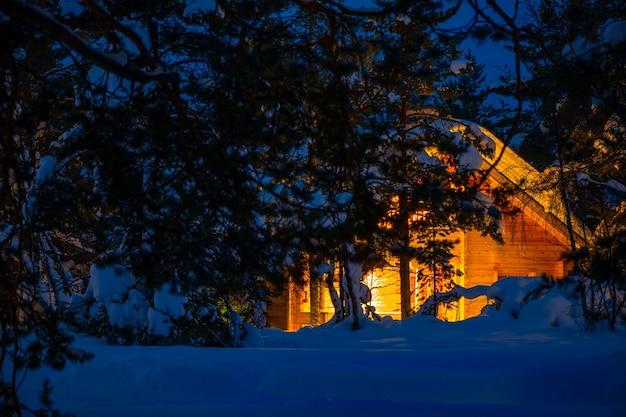 Houten huis in het bos van de nachtwinter. heel veel sneeuw