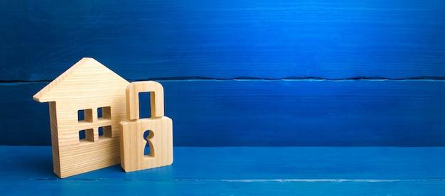 Houten huis met een hangslot. huis met een slot. beveiliging en veiligheid, onderpand