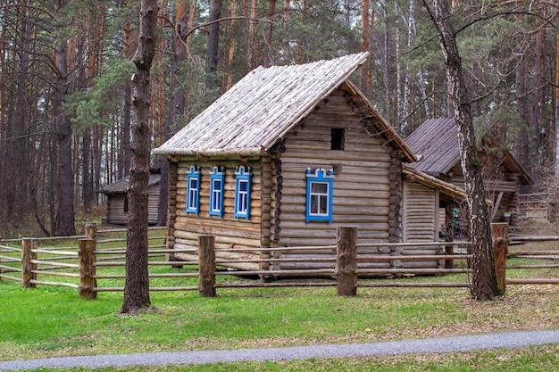 Houten huis met een herenhuis in het bos. de woning is voorzien van geschilderde ramen. een houten brug leidt naar het huis over de rivier.