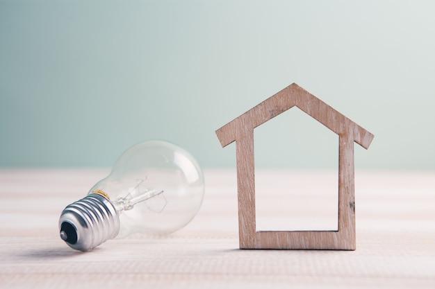 Houten huis met gloeilamp op tafel, een symbool voor constructie, creatief gloeilampidee