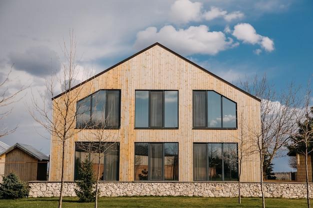 Houten huis met grote ramen in een dorp op blauwe hemelachtergrond