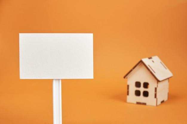 Houten huis model en leeg teken op bruine achtergrond kopie ruimte onroerend goed concept