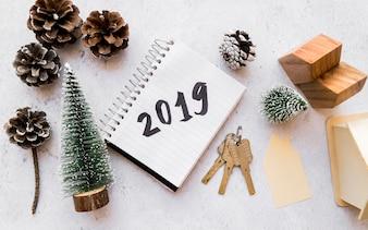 Houten huis model; kerstboom; dennenappels; sleutels en 2019 geschreven op spiraalvormige blocnote tegen concrete achtergrond