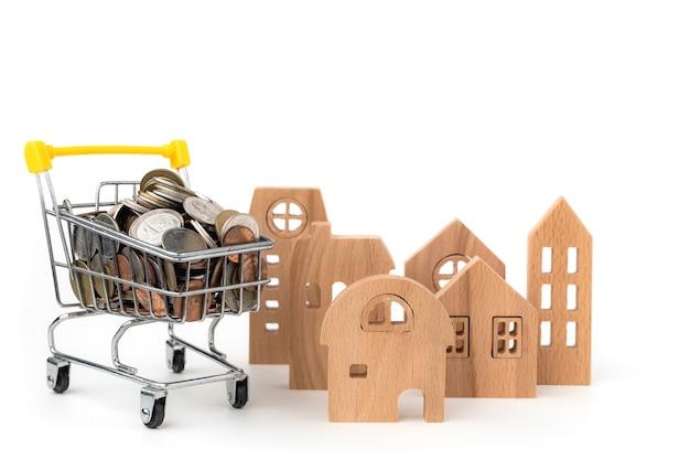 Houten huis model met vol munten in winkelwagen op wit geïsoleerd voor zaken, financiën en onroerend goed investeringen concept