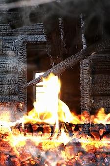 Houten huis na de brand. kolen op de logboeken. de as van het huis van het vuur. verbrand verwoest huisje.