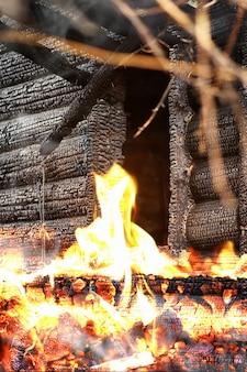 Houten huis na de brand. kolen op de logboeken. de as van het huis van het vuur. verbrand verwoest huisje. Premium Foto