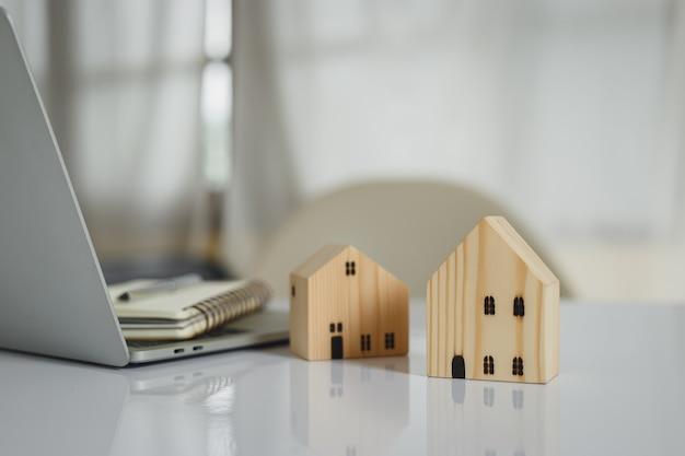 Houten huis op kantoortafel, vastgoedinvestering, sparen voor de toekomst, geldinvestering voor koophuis. investeringen bedrijfsconcept.