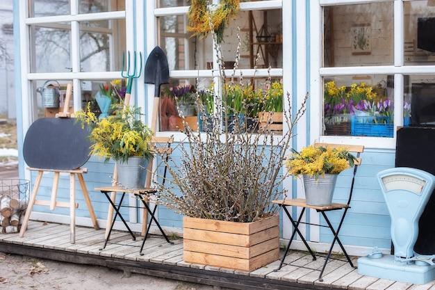 Houten huis veranda met bloemen, planten en stoelen