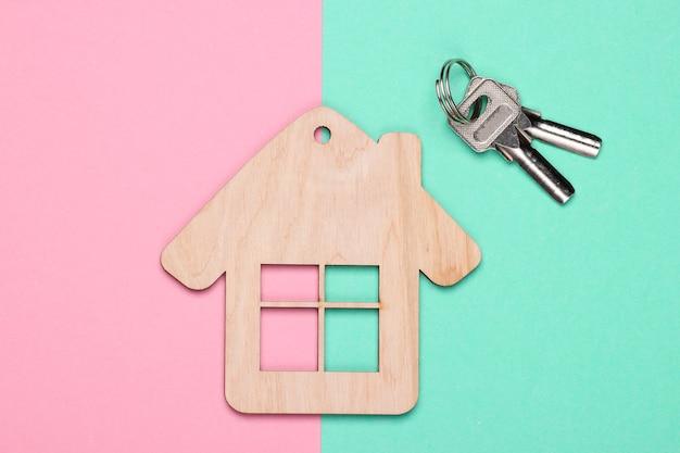 Houten huisbeeldje of sleutelhanger met sleutels op blauw roze achtergrond. bovenaanzicht