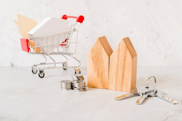 Houten huisblokken; stapel munten; sleutels en een klein winkelwagentje op concrete achtergrond