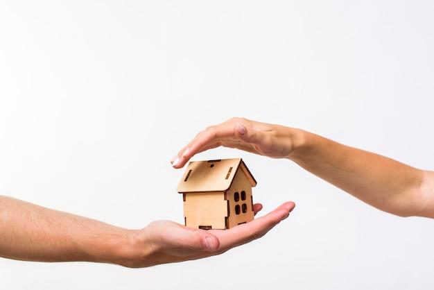 Houten huisje beschermd door handen