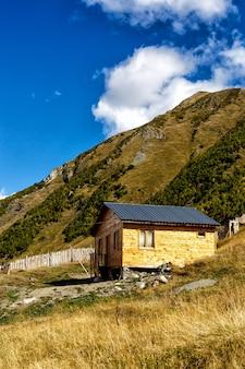 Houten huisje in de voet van bergen