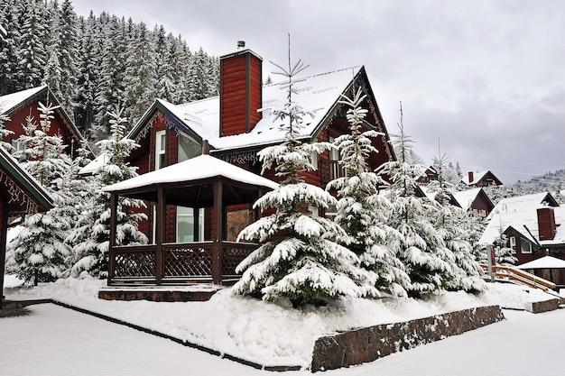 Houten huisje vakantiehuis in vakantieoord in de bergen bedekt met verse sneeuw in de winter.