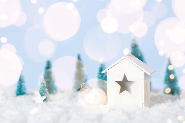 Houten huiskerstmis met decirations op witte sneeuwachtergrond