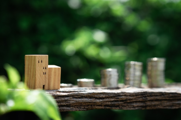Houten huismodel en rij van muntgeld op houten lijst met de aardbackgro van onduidelijk beeld groene bladeren