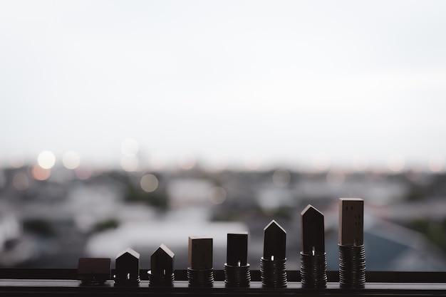 Houten huismodel en rij van muntgeld op houten lijst met de achtergrond van de onduidelijk beeldstad, echte estat