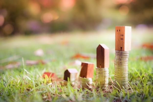 Houten huismodel en rij van muntgeld op houten lijst met de achtergrond van de onduidelijk beeldstad,