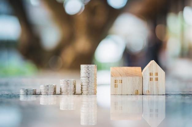 Houten huismodel en rij van muntstukgeld op witte achtergrond, real estate-markt, handelgoed, hypotheekconcepten