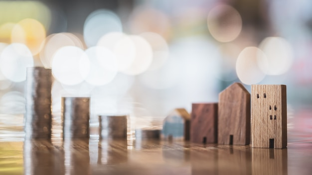 Houten huismodel en rij van muntstukgeld op witte achtergrond