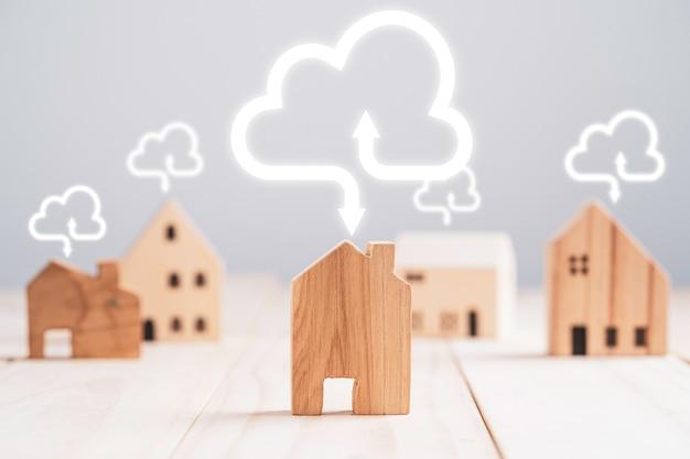 Houten huismodel met virtuele cloud computing, upload en download informatiegegevensapplicatie en technologietransformatieconcept.
