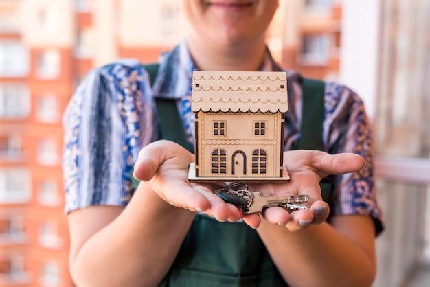 Houten huismodel met vrouwelijke handen en sleutels