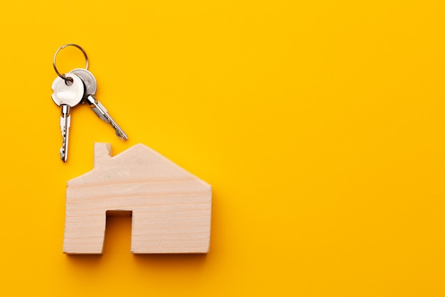 Houten huismodel miniatuur en huissleutels close-up