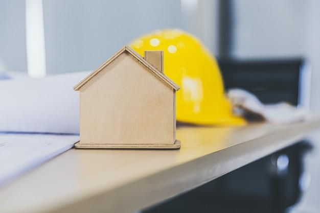 Houten huismodel op bureau bij bouwplaatskantoor