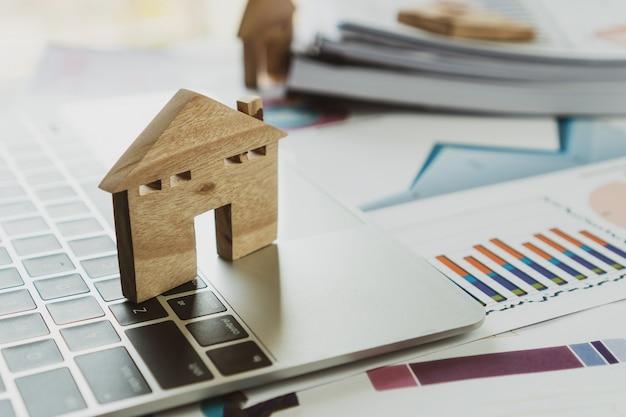 Houten huismodel op computer en grafiekrapport, de hypotheeklening van bezitsonroerende goederen of investeringsconcept
