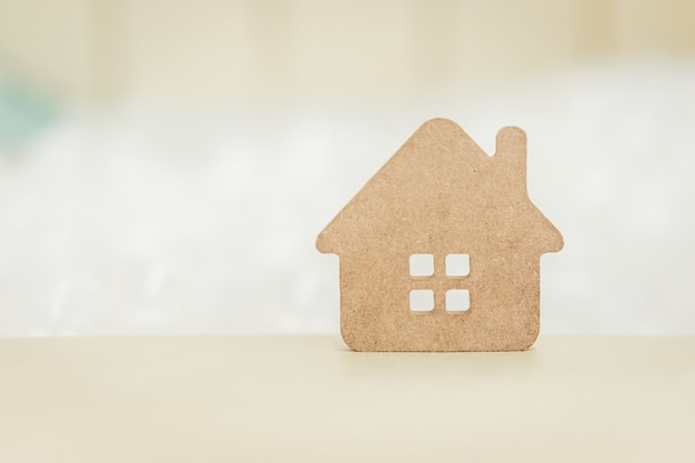 Houten huismodel op houten achtergrond,