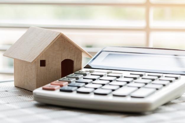 Houten huismodel op rekenmachine voor budgetbetaling of huis kopen. ideeën voor onroerend goed in onroerend goed