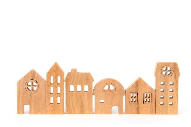 Houten huismodel op wit dat voor huisvesting en bezitsconcept wordt geïsoleerd