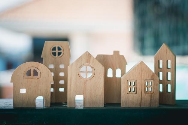 Houten huismodel tegen wazig buiten voor huisvesting en eigendomsconcept