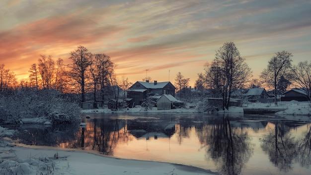Houten huizen aan de oevers van de vuoksa-rivier in de stad priozersk, rusland bij zonsopgang in de winter