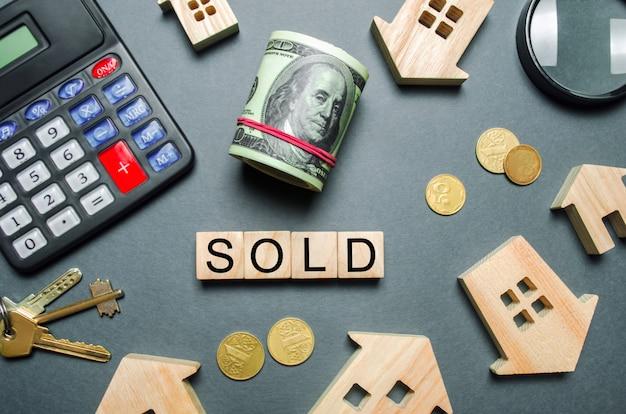 Houten huizen, een rekenmachine, sleutels, munten en blokken met het verkochte woord.