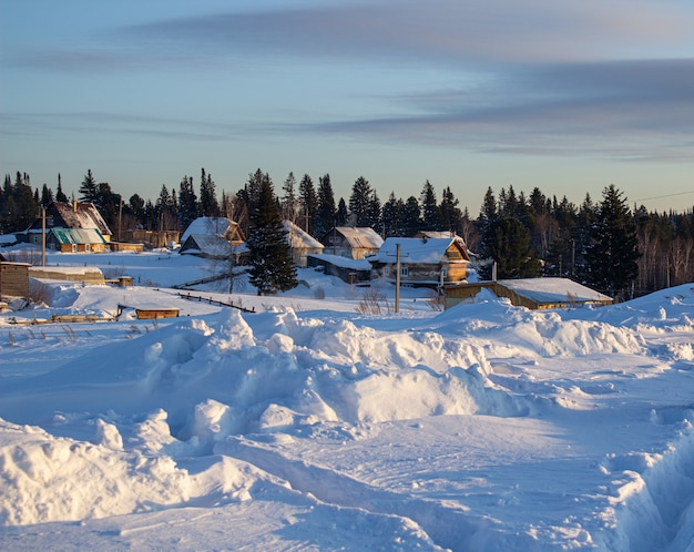 Houten huizen en hekken bedekt met sneeuw in siberië, rusland.